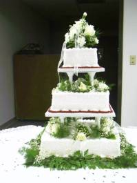 Square wedding cake with buttercream and greenery